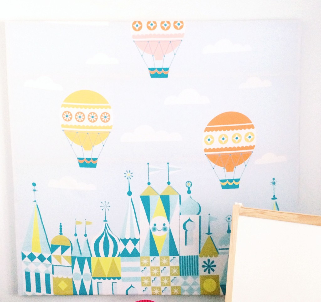 A DIY piece of canvas art displaying a cartoony version of three balloons and a pointed building tops.